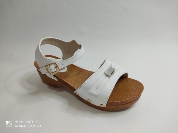 Sandalia para niña con suela imitación madera y tacón. Pala blanca con un lazo sobre los dedos. Talón sujeto con cierre con hebilla.