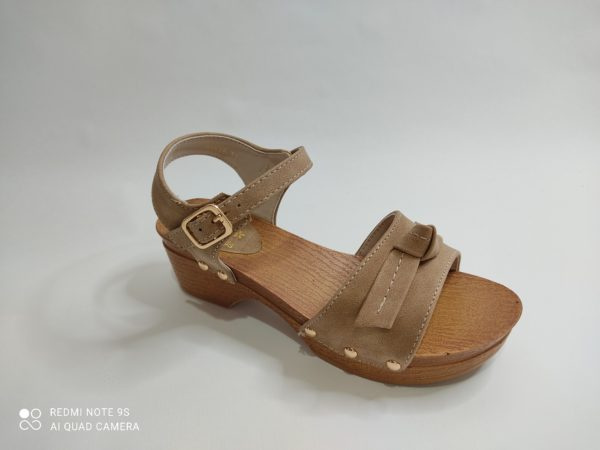 Sandalia de niña en color taupe. La suela imita la madera. Tacón ancho. Pala en color taupe con un lazo sobre los dedos. Cierre con hebilla sobre el tobillo.