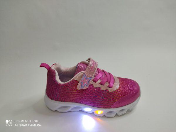 Zapatillas niña con luces en la suela. Color fuxia con líneas de purpurina. Cordón elástico en color fuxia y velcro- Puntera reforzada en fuxia.