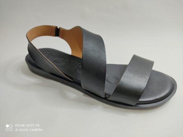 Sandalia plana en color negro de la marca Chica 10. Plantilla de gel. Una tira ancha de piel sobre los dedo, otra cruzada sobre el empeine y la ultima rodeando el talón.