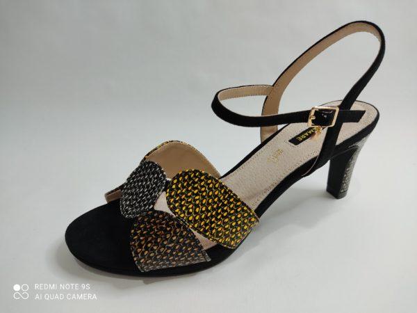 Sandalia negra de tacón medio. Pulsera en el tobillo. La parte delantera consta de 4 tiras anchas unidas por una circulo central. Todas las tiras están salpicadas por puntitos blancos, amarillos y ocres.