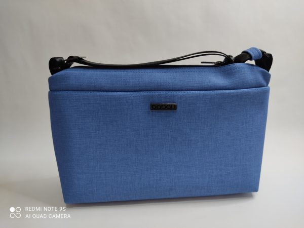 Bolso bandolera Babau con forma rectangular. Correa regulable confeccionada con cinturones de seguridad. En su interior hay un botón que accionándolo se enciende una luz interior. Exterior en color azul.