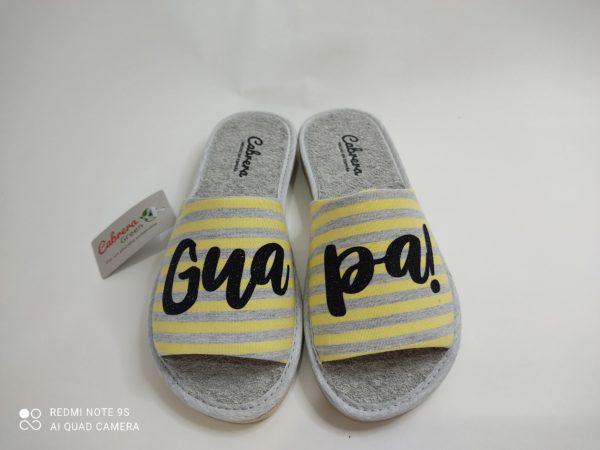 """Zapatillas de casa de mujer con suela pómez que no dejan huella. Plantilla de rizo gris que absorben el sudor. Pala en lineas gris y amarillo con el logo """"Guapa!"""" en purpurina negra."""
