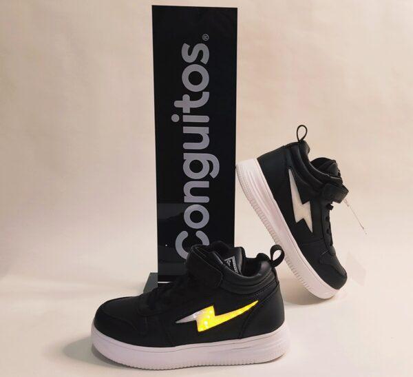 Botín de la marca Conguitos, modelo Ll22401en color negro. Fabricado en napa negra. Detalle de un rayo en el lateral de color blanco que se ilumina con luces amarillas al caminar. Cierre con elástico y velcro en el empeine. Suela color blanca.
