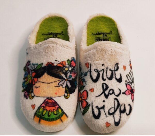 """Zapatillas de casa de la marca Vivant, modelo Frida Kahlo. Zapatillas aterciopeladas en color beige, plantilla extraíble y suela antideslizante. En el píe derecho la imagen de Frida Kahlo y en izquierdo la leyenda """"Vive la vida""""."""